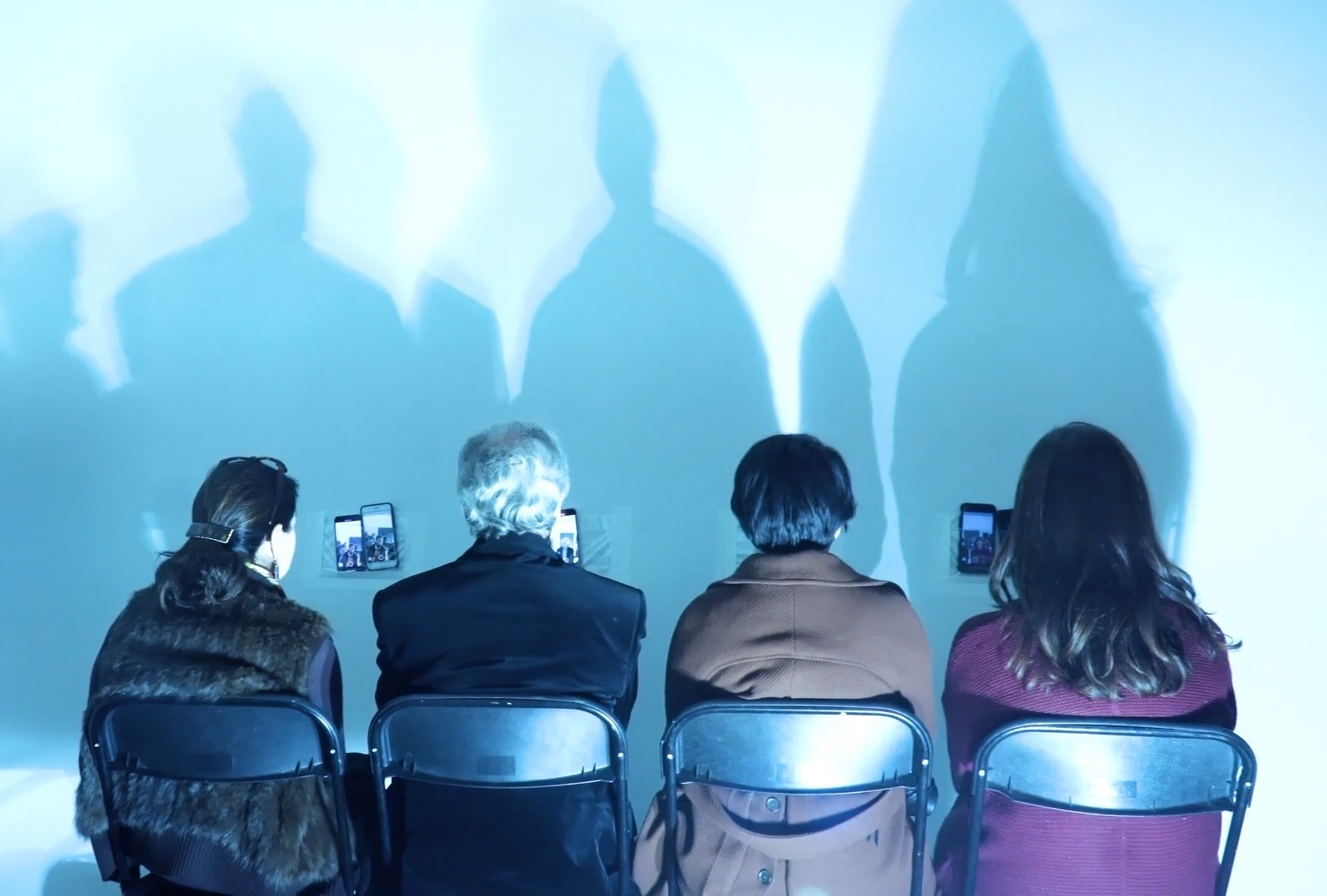 Four audience members stay seated facing the wall looking at their image on their phones mounted on the wall in a clear sleeve. The lighting produces four shadows along the wall.